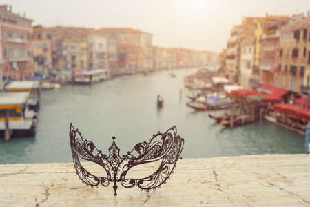 Venetian masks on bridge agaist beautiful landscape Grand Canal with gondolas and boats in Venice, Italy . Annual carnival in Venice is among the most famous in Europe. Venice is a popular tourist destination of Europe. 版權商用圖片