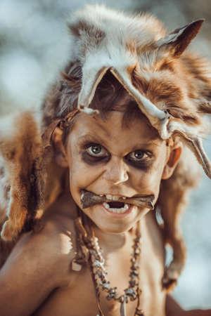 Boos grappig jongensportret. Kleine holbewoner met bot in mond. Prehistorische tribal jongen buiten op de natuur. Jonge ruige en vuile wilde, krijger en jagersgezicht. Primitieve ijstijd man in dierenhuid close-up.