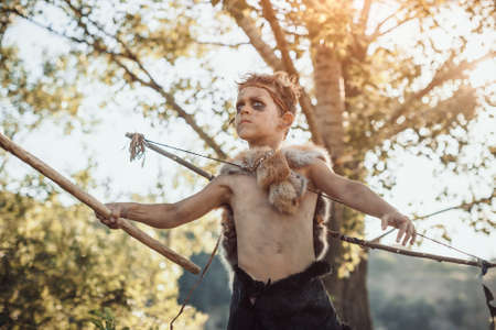 Caveman, manly boy with weapon aggressively shouting. Dramatic action photo of young primitive boy outdoors in forest. Evolution survival concept. Calm boy outside standing in attack pose. Prehistoric tribal man outside on wild nature. Primitive ice age man in animal skin with bow and staff. Creative art fantasy photo. 版權商用圖片