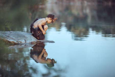 Holbewonerjongen die op de rots zit en naar zichzelf kijkt in de waterreflectie in het meer. Evolutie overlevingsconcept. Creatieve kunst fantasie foto