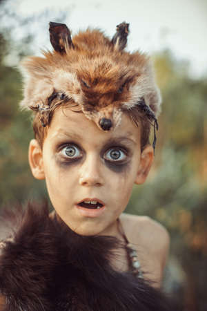 Surprised funny boy portrait. Little caveman with open mouth. Prehistoric tribal boy outdoors on nature. Young shaggy and dirty savage, warrior and hunter face. Primitive ice age man in animal skin close-up.