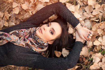 Autumn girl in city park. Portrait of an autumn woman lying over leaves and looking at camera outside in fall forest. Beautiful mixed race Caucasian Asian young woman. Reklamní fotografie