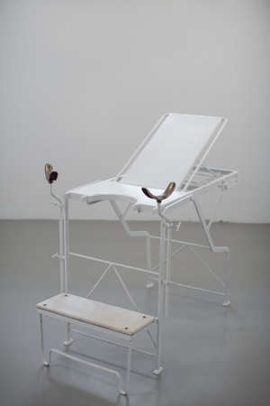 Old style chair for women diagnosis agaist white wall. Gynie exam table in museum. 스톡 콘텐츠