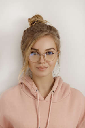 Hipster young girl over wall. Portrait of a cute positive seductive fashion model in street style smiling posing indoors. Beautiful blond woman wearing pink hoody and stylish glasses standing and looking at camera agaist light gray background.