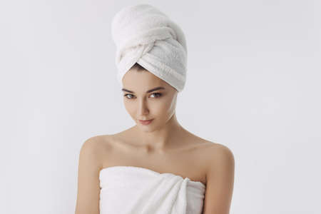 Beautiful young woman in white towel after bath on white background. Portrait of happy mixed race Caucasian Asian slim wgirl posing indoors in studio. Perfect model looking at camera
