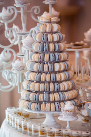 Luxury wedding candy bar table set. Macaron tower or pyramid and cupcakes on sweet dessert table. Pastel stylish colours., sweets, treats 写真素材