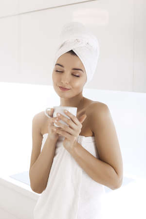 Young woman after bath or shower enjoying coffee indoors at home. Young Mixed race Caucasian Asian woman with perfect makeup in white towel with cup of coffe or tea on modern light kitchen. Cheerful young woman smiling, dreaming with closed eyes. 스톡 콘텐츠