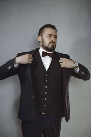 Mans style. Elegant young bearded man getting ready, dressing suit against gray grunge background. Fashion vogue photo. Close-up portrait of the man in a luxury classic trendy suit, vest, shirt.