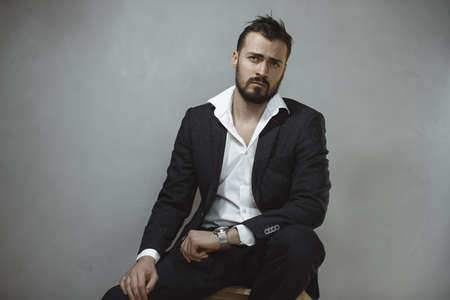 Modern businessman. Confident brutal man in a trendy suit looking away, sitting on a chair indoors against the empty concrete wall. Portrait of a bearded attractive gentleman in elegant stylish clothes on gray background. Fashion shot.