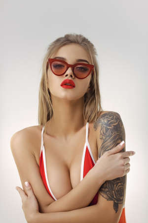 Glamour beach woman with perfect makeup wearing red bikini and retro sunglasses isolated on bright copy space background in studio. Portrait of gorgeous woman standing and posing in stylish swimsuit indoors. Concept of summer holidays and traveling.