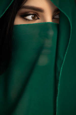 Beautiful Arabian woman portrait traditional costume indoors. Young Hindu woman. Close-up portrait of beauty model with bright makeup who hiding her face behind transparent veil standing over dark background. The model looking away
