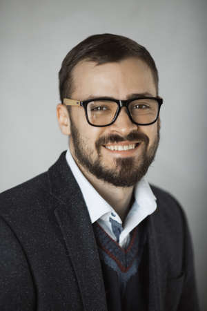 Portrait of handsome smiling businessman wearing casual black suit blue sweater white. shirt and glasses. Fashion stylish man standing against gray wall indoors. Close-up portrait of a bearded attractive gentleman in an elegant stylish clothes. Stock Photo