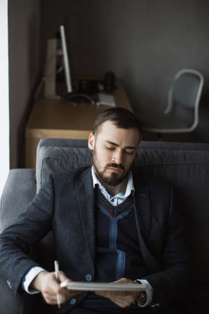 Confident concentrated handsome bearded businessman in a trendy suit reading important ideas in a notebook sitting on a sofa in the office. Absorbedly thinking. Serious man in business wears working. Stock Photo