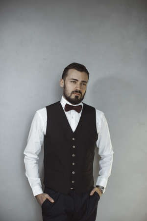 Happy handsome smiling man in a black vest and bow tie looking away. Portrait of a bearded attractive gentleman in elegant stylish clothes on gray grungy background.