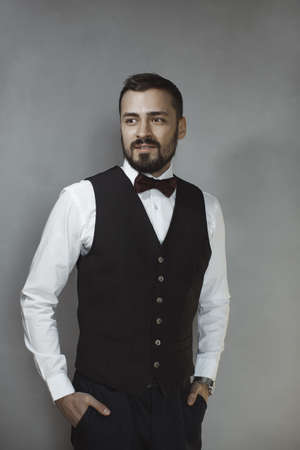 Happy handsome smiling man in black vest and bow tie looking away. Portrait of a bearded attractive gentleman in elegant stylish clothes on gray background.