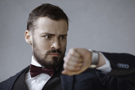 We have no more time. Portrait of the handsome serious bearded young man in trendy suit black vest and white shirt, standing, looking at the watch with worried facial expression. Indoor shot, isolated on grey background. Business and time management concept. Stock fotó