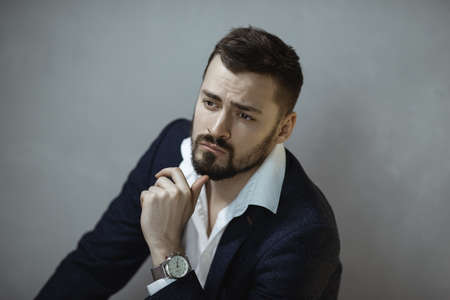 Modern businessman. Confident thinking man in a trendy suit looking at the camera, sitting indoors against the empty concrete wall. Close-up portrait of a bearded attractive gentleman in elegant stylish clothes on gray background. Fashion shot.