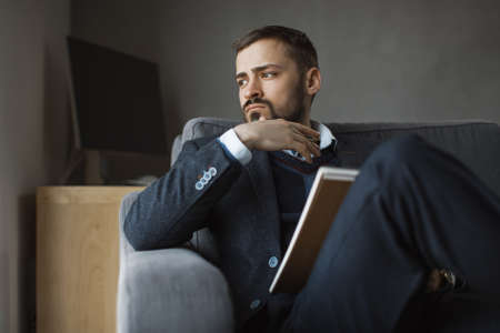 Confident concentrated handsome bearded businessman in a trendy suit holding notebook sitting on a sofa in the office. Absorbency thinking. Serious man in business wears working. Window desk and computer on the background.