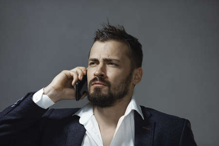 A handsome young businessman talking on smartphone indoors against a gray background. Portrait of a bearded concentrated man speaking on phone looking away.