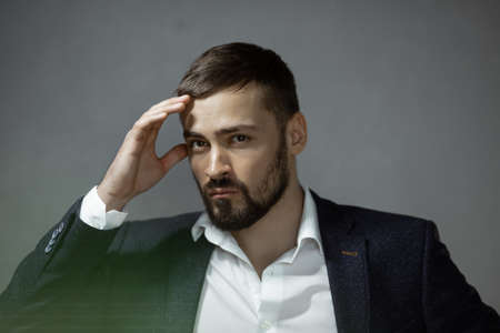 Modern businessman. Confident young man in a trendy suit looking at the camera, standing indoors against the empty concrete wall. Close-up portrait of a bearded attractive gentleman in elegant stylish clothes on gray background. Fashion vogue shot.