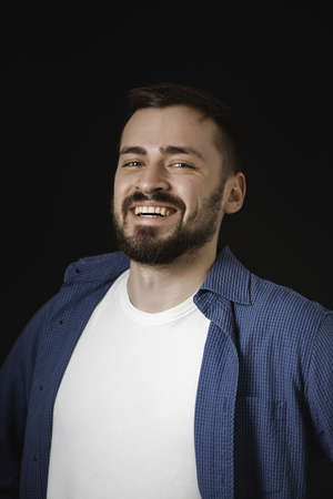 Happy young man. Portrait of a handsome young bearded man in casual blue shirt smiling looking into the camera isolated on black studio background. Copy space for text.