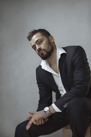 Modern businessman. Confident brutal man in a trendy suit looking at the camera, sitting on a chair indoors against the empty concrete wall. Portrait of a bearded attractive gentleman in elegant stylish clothes on gray background. Fashion shot.