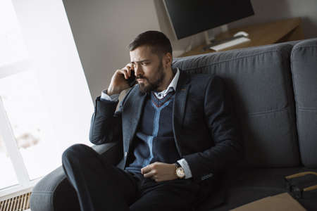 Cheerful businessman in suit talking on the phone, sitting on sofa in office. Portrait of a bearded concentrated man speaking on phone looking away.