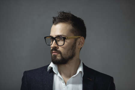 Modern businessman. Confident young man in a trendy suit and glasses looking away, standing indoors against the empty concrete wall. Close-up portrait of a bearded attractive gentleman in elegant stylish clothes on gray background. Fashion vogue shot.