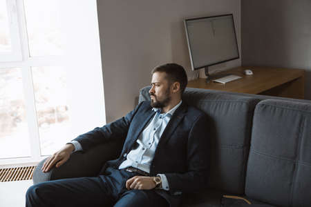 Thinking Ideas Strategy Working Concept. Modern businessman. Confident young man in a trendy suit looking away while sitting indoors on the sofa against the empty concrete wall. Close-up portrait of a bearded attractive gentleman in an elegant stylish clothes.