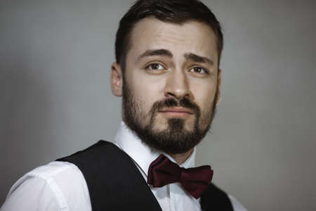 Happy handsome smiling man in a black vest and bow tie looking away. Close-up portrait of a bearded attractive gentleman in elegant stylish clothes on gray grungy background.