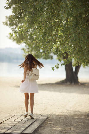 Back view of young beautiful woman in a white dress resting with a backpack on the beach.
