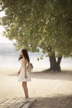 Young beautiful woman in a white dress standing with a backpack on the beach. Stockfoto