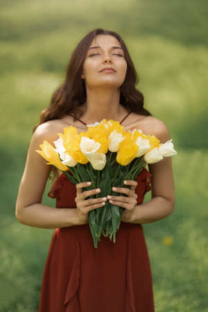 Attractive woman in red dress with a bouquet of spring flowers against nature bokeh green background.