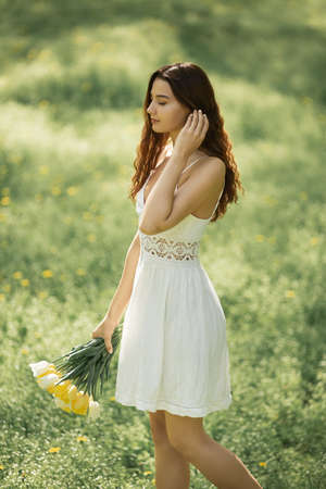 Attractive woman in white dress with a bouquet of spring flowers walking against nature bokeh green background.