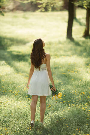 Rear view og attractive woman in white dress with a bouquet of spring flowers walking against nature bokeh green background. Stock fotó