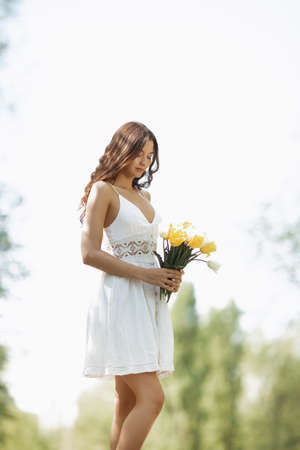 Attractive woman in white dress with a bouquet of spring flowers standing against nature bokeh green background.