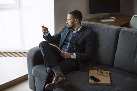 Thinking Ideas Strategy Working Concept. Modern businessman. Confident young man in a trendy suit looking away while sitting indoors.