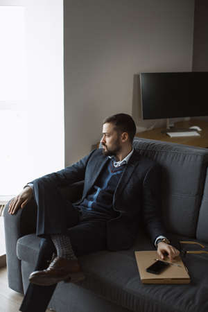 Confident young man in a trendy suit looking away while sitting indoors on the sofa. Close-up portrait of a bearded attractive gentleman in an elegant stylish clothes. Stockfoto