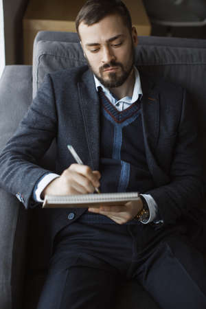 Confident concentrated handsome bearded businessman in a trendy suit writes down important ideas in a notebook sitting on a sofa in the office. Absorbedly thinking. Serious man in business wears working.