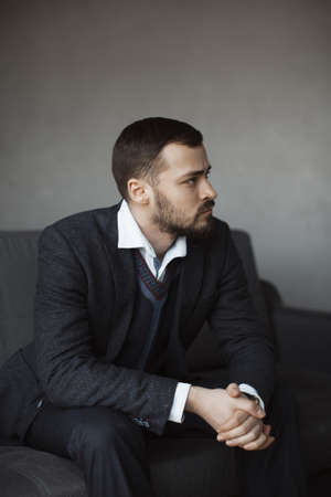 onfident young man in a trendy suit looking away while sitting indoors on the sofa against the empty concrete wall. Portrait of a bearded attractive gentleman in an elegant stylish clothes. Stockfoto