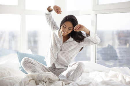 Happy woman stretching in bed. Attractive Asian girl in nightgown sitting against big window and waking up in the bedroom on sunny morning. Good morning concept. Banque d'images - 129597362