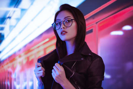 Fashion beauty shooting of gorgeous Asian model. Young beautiful woman in black jacket posing over night city dramatic red and blue neon background