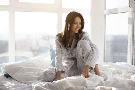 Junge schöne asiatische Frau wachte am sonnigen Morgen auf. Attraktives Mädchen im Nachthemd, das zu Hause auf dem Bett gegen großes Fenster sitzt. Wunderschönes Model, das wegschaut