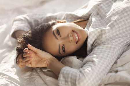 Happy woman stretching in bed in the morning. Attractive Asian girl in nightgown waking up in the bedroom on sunny morning. Good morning concept Banque d'images - 129597551