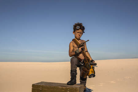 Post-apocalyptic boy outdoors in the desert. Nuclear post-apocalypse. Life after doomsday concept. Desert and dead wasteland on the background. A young man with gun, knife, gas mask, mug standing on a chest