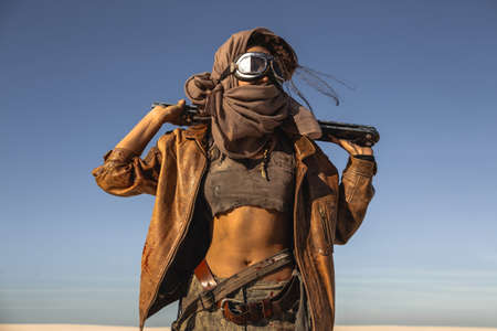 Post-apocalyptic woman with weapon outdoors. Young slim girl warrior in shabby clothes holding sword standing in a confident pose looking away. Nuclear post-apocalypse time. Life after doomsday concept. Desert and dead wasteland on the background. Closeup portrait.