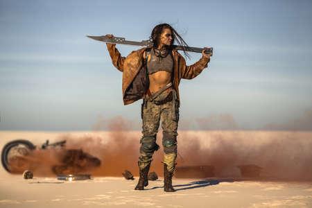 Postapokalyptische Bikerfrau mit Waffe im Freien. Junge schlanke Kriegerin in schäbiger Kleidung, die das Schwert in einer selbstbewussten Pose gegen das kaputte brennende Motorrad hält, das wegschaut. Nukleare Zeit nach der Apokalypse. Leben nach dem Weltuntergangskonzept. Wüste und totes Ödland im Hintergrund. Nahaufnahmeportrait.
