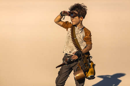 Post apocalyptic fighter boy outdoors in the desert. People in nuclear post-apocalypse. Life after doomsday concept. Desert and dead wasteland on the background. A young man in shabby clothes with gun, knife, gas mask, mug Stockfoto