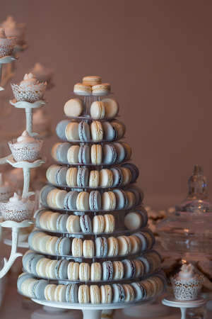 Luxury wedding candy bar table set. Macaron tower or pyramid and cupcakes on sweet dessert table. Pastel stylish colours., sweets, treats Stock fotó