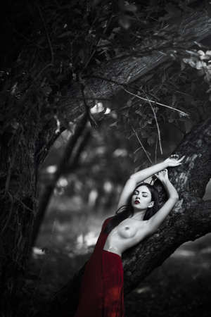Sensual sexy fashion model with naked breast resting in fantastical forest. Photo of seductive nude woman in luxury long red dress laying on tree. Multi-racial Asian Caucasian girl. Fashionable toning. Creative computer colors. Stock Photo